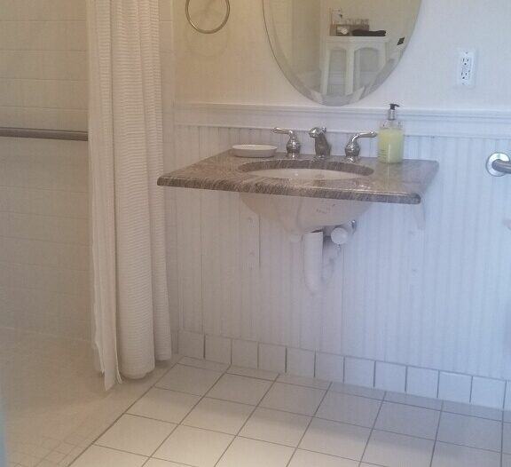 Sink allows wheelchair movement underneath.